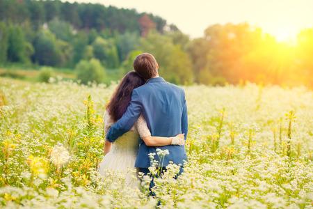 カメラに戻って草原で抱き締める若い幸せな結婚式のカップル