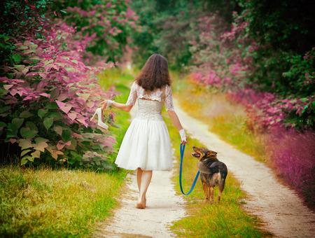 pies descalzos: La mujer joven recorre descalzo con el perro en el camino rural