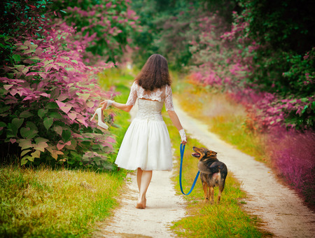 Young woman walks barefoot with dog on rural road photo