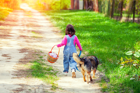 Little girl walking with dog on the road back to camera and keeping the dog on leash photo