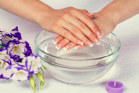 Beautiful female hands with perfect french manicure in bowl of water decorated with flowers