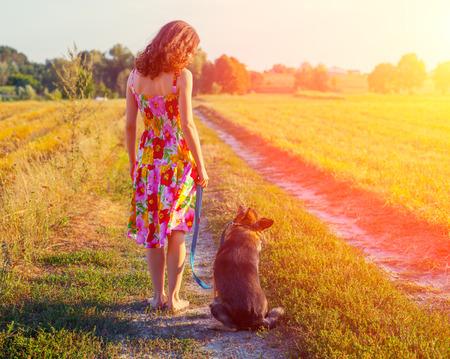 pies descalzos: Mujer joven caminando descalzo con el perro en el camino rural de nuevo a la c�mara.
