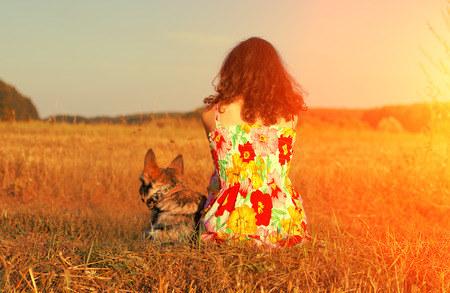 Young woman with dog in the field at sunset light back to camera. photo