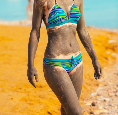 Young pretty woman smeared with Dead Sea mud on the beach photo