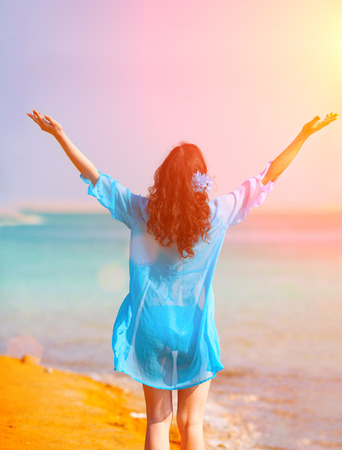 meditative: Happy young woman with hands up walking on Dead Sea seashore Stock Photo