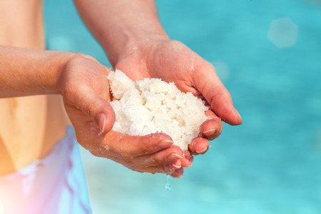 mineral salt: Female hands with sea salt for spa from Dead Sea
