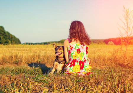 Young woman with dog in the field at sunset light back to camera photo