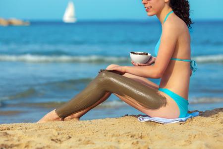 Jonge vrouw houdt kom met Dode Zee modder op de kust Stockfoto