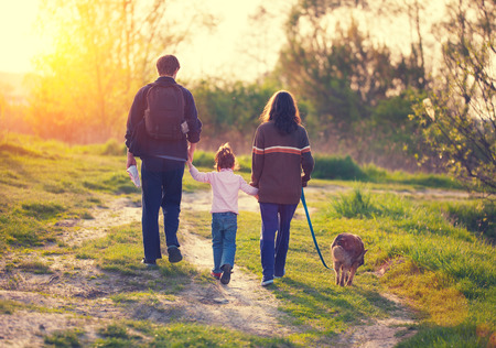 Family with dog walking in the village at sunset back to camera