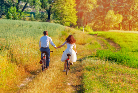 Save to a lightbox  Find Similar Images  Share Stock Photo: Young happy bride and groom ride bicycles in the meadow back to camera and holding hands
