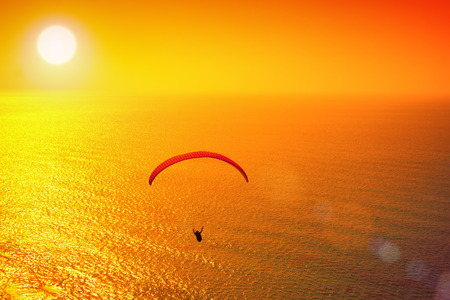 paraglider: Silhouette of paraglider soaring over sea at sunset