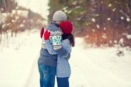 Young couple in lowe hugging outdoors in snowy winter
