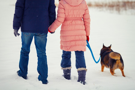 Young happy couple with dog walking in the snowy field back to camera photo