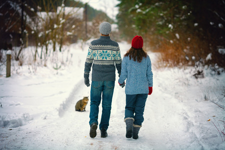 Young couple in love holding hands walking on the snowy road in village photo