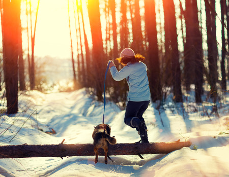 walking boots: Young woman with dog jumping over a log