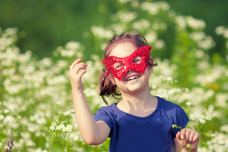 freedom nature: Happy little girl wearing a red mask on the flower meadow Stock Photo
