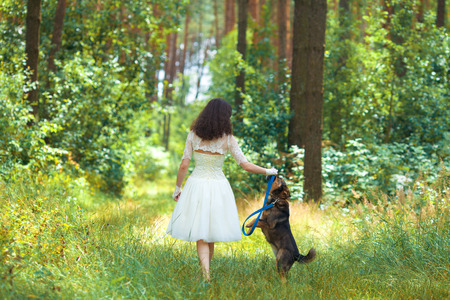 Young bride walking with dog on the rural road photo