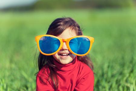 フィールドに大きなサングラスをかけて幸せな笑みを浮かべて少女 写真素材