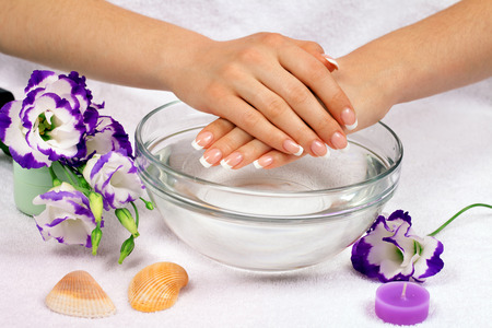 manicure: Beautiful female hands with perfect french manicure in bowl of water decorated with flowers
