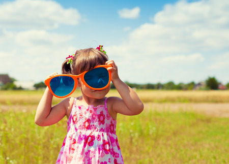 Happy little girl with big sunglasses walking on the field