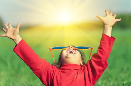 sol radiante: Niña feliz vistiendo grandes gafas de sol con las manos arriba disfrutando del sol en el campo Foto de archivo