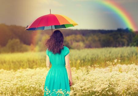 公正な天気で傘の下でフィールド上を歩く若い女性