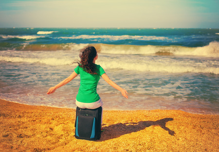 siting: Young happy girl siting on the traveling bag on the beach Stock Photo