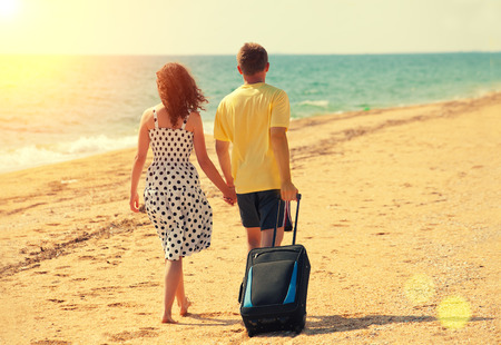 bags in hands: Young couple with travel bag holding hands, walking on the beach back to camera Stock Photo