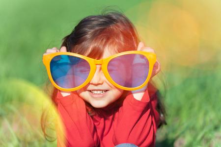 ni�os riendo: Feliz sonriente ni�a llevaba gafas de sol grandes en el campo