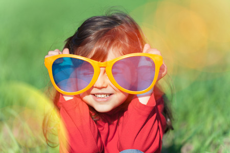 a child: Happy smiling little girl wearing big sunglasses in the field