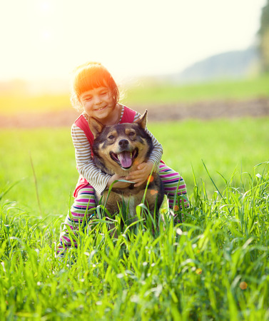 Happy little girl riding her dog on the field Imagens
