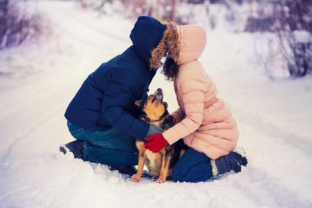 enamorados besandose: Joven pareja de enamorados que se besan en el campo cubierto de nieve Foto de archivo