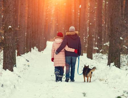 caminando: Joven pareja feliz con el perro caminando en el bosque de invierno de nuevo a la cámara