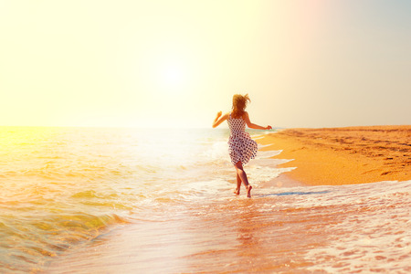 woman beach dress: Happy girl running on the beach towards the sun
