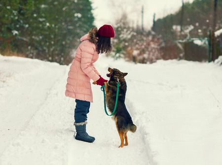 snow day: Pretty young woman training her dog in winter Stock Photo