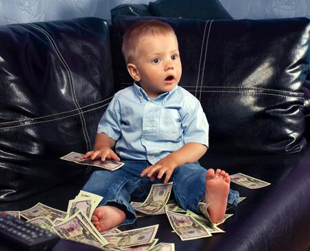 fake money: Thinking little boy with fake money