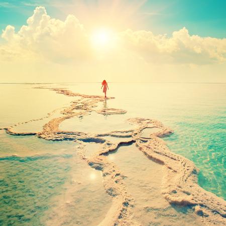 Silhouet van de jonge vrouw lopen op de Dode Zee Stockfoto