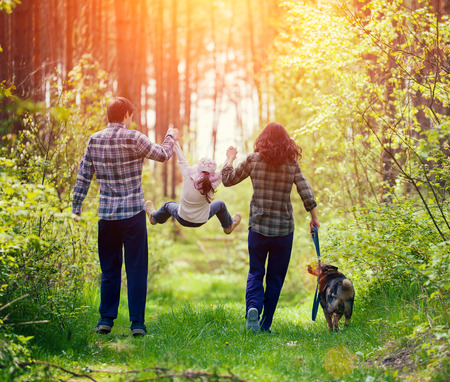 familias jovenes: Familia feliz que recorre con el perro en el bosque