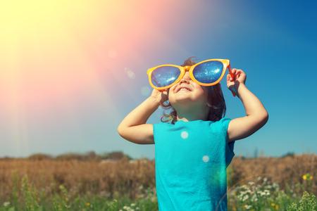 sol radiante: Niña con grandes gafas de sol disfruta de sol Foto de archivo