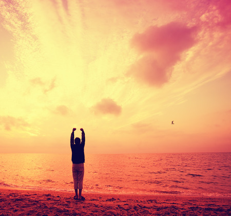 Silhouette of young man with hands in the air on the beach at sunrise Stock Photo