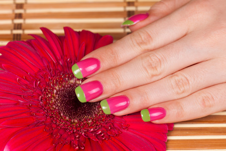 Beautiful female hand with perfect french manicure on bamboo pad and flower photo