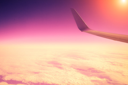 Airplane flying above clouds at pink sunrise photo
