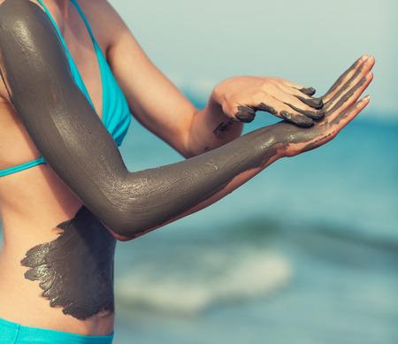 Woman smearing mud mask on the body Standard-Bild
