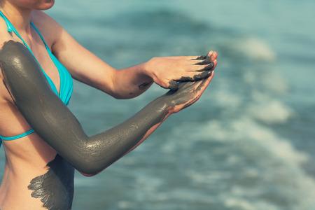 Woman smearing mud mask on the body Foto de archivo