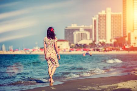 Jonge vrouw lopen terug naar camera bij zonsondergang op het strand in Tel Aviv, Israël