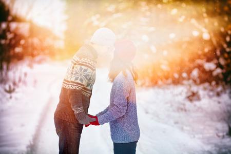romantique: Jeune couple heureux en amour tenant les mains et embrassant l'extérieur en hiver enneigée au coucher du soleil