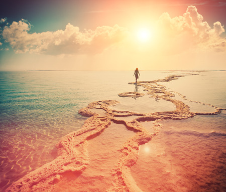 morning sunrise: Silhouette of young woman walking on Dead Sea Stock Photo