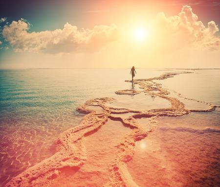 horizonte: Silueta de la mujer joven que recorre en Mar Muerto