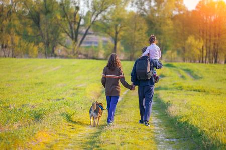 犬を連れて歩いて幸せな家族 写真素材