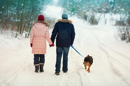 puppy love: Pareja joven con el perro que recorre en el pueblo nevado espaldas a la c�mara Foto de archivo